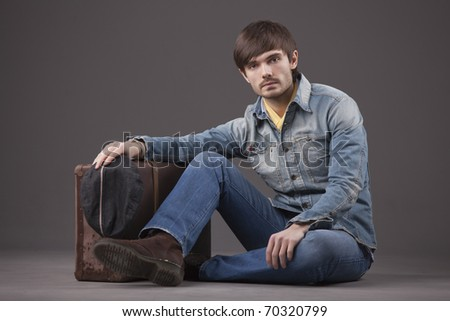 male model in denim clothes sitting on the ground with old suitcase