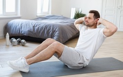 Male Morning Workout. Sporty Man Doing Sit-Ups Abs Exercise On Gymnastics Mat Training And Working Out In Bedroom At Home. Fitness Lifestyle Motivation, Stay Fit Concept