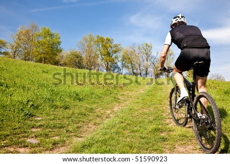 Male mountain bike cyclist riding uphill along a country road; clear summer day, horizontal frame