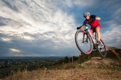 Male mountain biker jumping against blue evening sky. Low angle portrait. Extreme sport donwhill cyclist