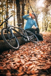 Male mountain biker sitting with bicycle in the forest. Drinking fresh water.