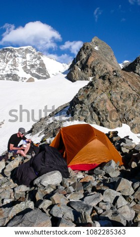 male mountain climber eating at base camp by an orange tent with a spectacular mountain landscape around him #1082285363