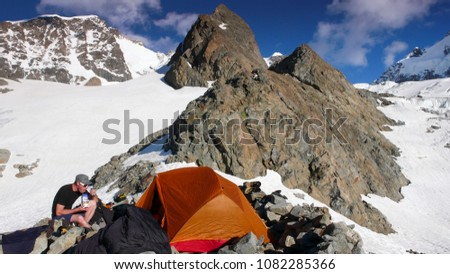 male mountain climber eating at base camp by an orange tent with a spectacular mountain landscape around him #1082285366