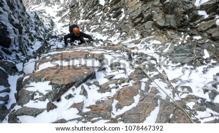 male mountain climber in a steep rock and ice couloir on his way to a high alpine summit #1078467392