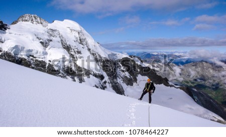 male mountain climber on a high alpine glacier with a great view of the fantastic mountain landscape behind him #1078464227