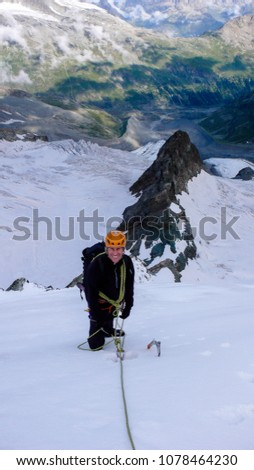 male mountain climber on a high alpine glacier with a great view of the fantastic mountain landscape behind him #1078464230