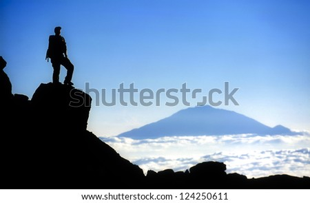 Male mountain climber standing on top of Mt Kilimanjaro with a view to Mt Meru. Mt. Kilimanjaro and Uhuru Peak at 5895m is the highest peak in Africa.