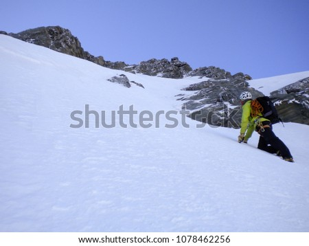 male mountain guide climbing a steep snow couloir on his way to a high summit in the Swiss Alps #1078462256