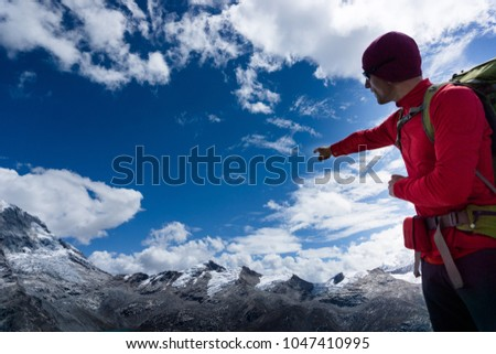 male mountain guide in red pointing to mountain peak panorama in the Andes in Peru