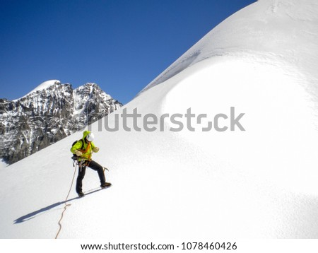 male mountain guide standing on a glacier on his way to a high summit in the Swiss Alps #1078460426