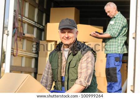 Male mover loading van with cardboard box delivery service