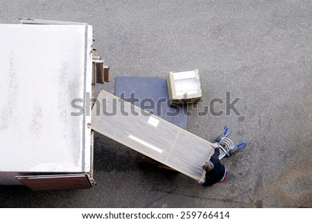 Male mover unload new furniture and boxes from moving truck. Situation with moving house worker, manually download the furniture from a back of a truck. View from above.