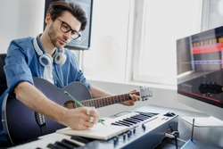 Male music arranger composing song on midi piano and audio equipment in digital recording studio. Man plays guitar and produce electronic soundtrack or track in project at home.