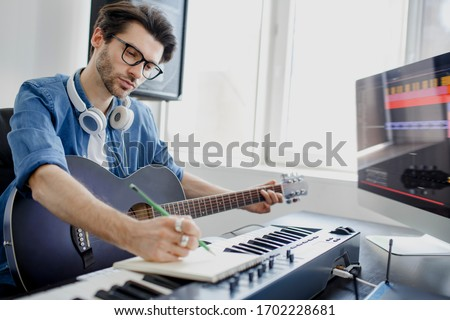 Male music arranger composing song on midi piano and audio equipment in digital recording studio. Man plays guitar and produce electronic soundtrack or track in project at home. Foto stock ©