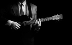 male musician in suit playing acoustic guitar, black and white. isolated on black