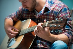 Male musician playing acoustic guitar