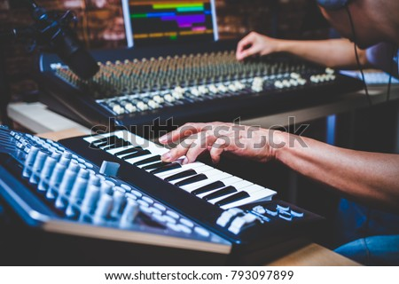 male musician playing midi keyboard synthesizer in recording studio, focus on hands - Shutterstock ID 793097899