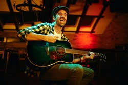 Male musician singing while playing acoustic guitar in a pub at night.