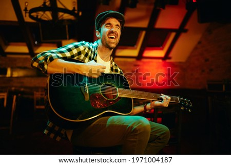 Male musician singing while playing acoustic guitar in a pub at night.  ストックフォト ©