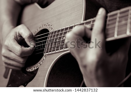 Male musicians playing acoustic guitar. Closeup musicians are playing acoustic guitar. Male musicians hold chords and strum guitar.