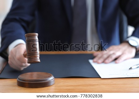 Male notary with judge hammer in office, closeup