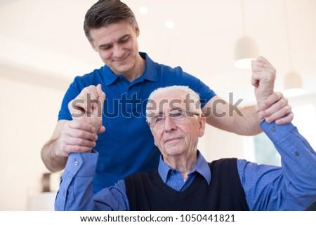 Male Nurse Assessing Senior Stroke Victim By Raising Arms #1050441821