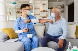 Male nurse greeting with senior male patient with mask while being in a home visit.