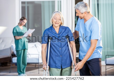 Male nurse helping senior woman to use crutches with caretaker in background at nursing home
