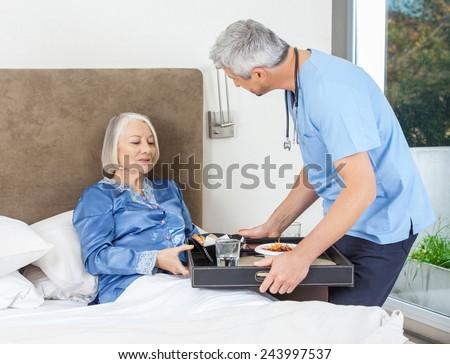Male nurse serving breakfast to senior woman on bed in nursing home