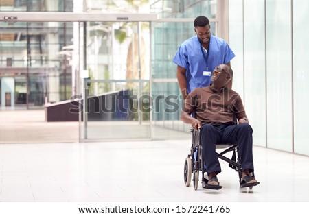 Male Nurse Wearing Scrubs Wheeling Patient In Wheelchair Through Lobby Of Modern Hospital Building Сток-фото ©