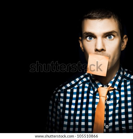 Male Office Administration Clerk Impersonating A Notice Board With Blank Orange Sticky Note On Face In A Copy Space Conceptual On Black Background - stock photo