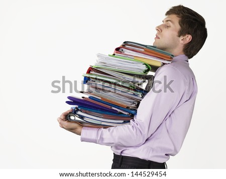 Male office worker carrying heavy binders against white background