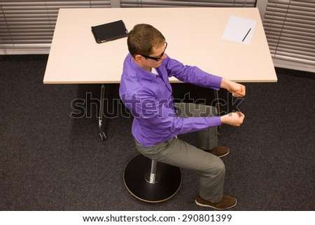 male office worker,exercising during short break in work at his desk in office