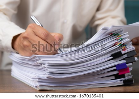 Male office workers with yellow shirt holding and writing documents on office desk, Stack of business overload paper.