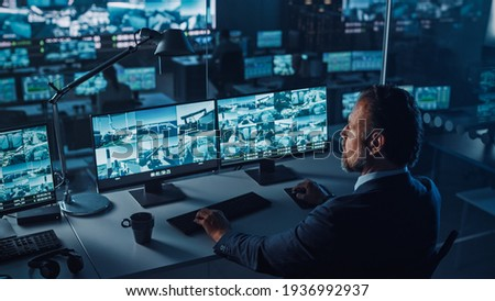 Male Officer Works on a Computer with Surveillance CCTV Video Footage in a Harbour Monitoring Center with Multiple Cameras on a Big Digital Screen. Employees Sit in Front of Displays with Big Data.