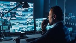 Male Officer Works on a Computer with Surveillance CCTV Video in a Harbour Monitoring Center with Multiple Cameras on a Big Digital Screen. Employee Uses Radio to Give an Order or Report.