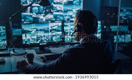 Male Officer Works on a Computer with Surveillance CCTV Video in a Harbour Monitoring Center with Multiple Cameras on a Big Digital Screen. Employees Sit in Front of Displays with Big Data.