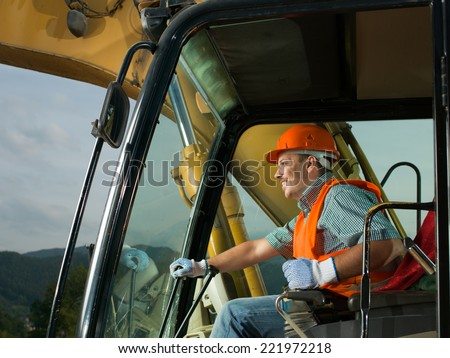 male operator driving excavator ...