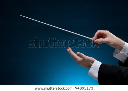 Male orchestra conductor hands, one with baton. Blue background.