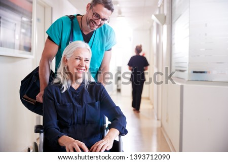 Photo of  Male Orderly Pushing Senior Female Patient Being Discharged From Hospital In Wheelchair