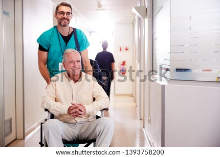 Photo of  Male Orderly Pushing Senior Male Patient Being Discharged From Hospital In Wheelchair