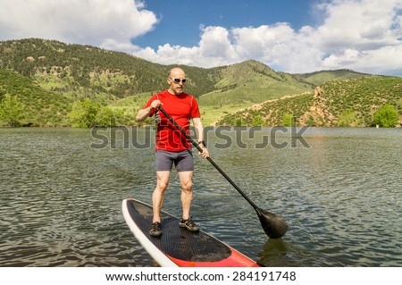 male paddler enjoying stand up paddling on a sunny summer day - Horsetooth Reservoir, Fort Collins, Colorado