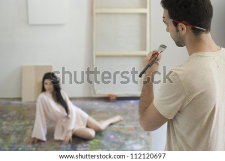 Male painter painting woman's sketch on canvas