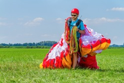 Male paraglider carrying mattress flyer in pasture