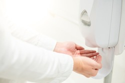 Male patient hands using automatic alcohol dispenser for cleaning hand in the hospital. Infection prevention concept. Save and clean in public medical center area.