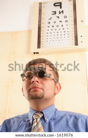 Male patient reading letters from the chart at the optician office