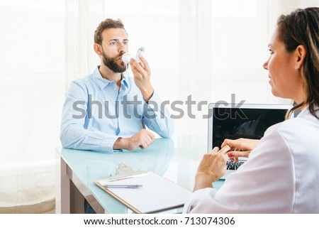 Male patient uses an aerosol inhaler placed on a space chamber at the doctor office Imagine de stoc ©