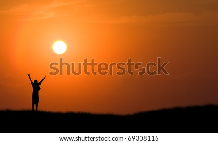male person boy jumping for joy silhouetted against orange setting sun sunset