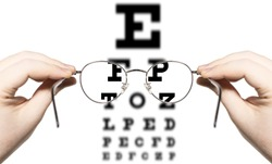 male person looking through glasses to eye examination test, letters inside the glasses are clear, others are blurred out, only hands are visible, first person point of view