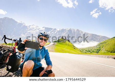 Male person takes a selfie on bicycle vacation in scenic caucasus mountain region. Travel in Kazbegi.
